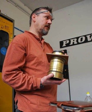 John Brewer with an antique camera lense