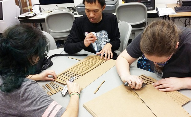 Yomna, Reza and Sophia preparing laser-cut piano keys for the rotary harmonograph
